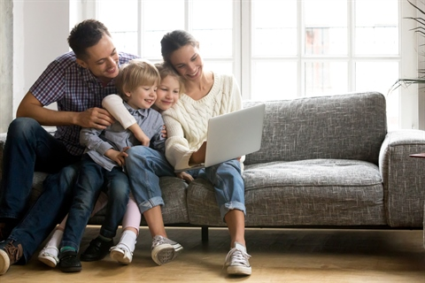Parents and children sitting on couch watching video on computer